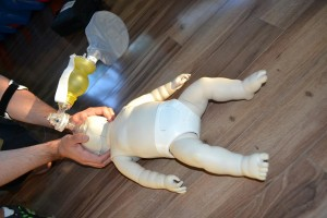 Pedatric bag valve mask and infant mannequin used to provide rescue breaths for CPR training.